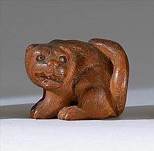 WOOD NETSUKE In the form of a seated tiger with glass inlaid eyes. Length 1.75