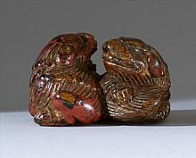 LACQUERED WOOD NETSUKE In the form of two shishi with red and gilt details. Length 2.1