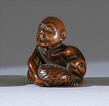 WOOD NETSUKE Depicting a blind stone lifter. Height 1.25