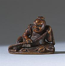 WOOD NETSUKE By Shoju. Depicting a nio tying a sandal. Length 1.6