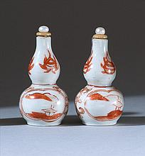 PAIR OF PORCELAIN SNUFF BOTTLES In double gourd form with rust-red landscape and passionflower design. Heights 2