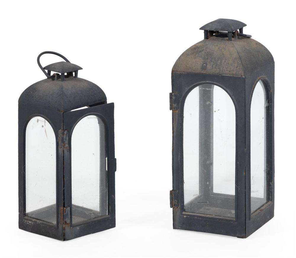 TWO MATCHING ARTS & CRAFTS-STYLE IRON LANTERNS Painted black. Domed tops with vents and bail handles. Square bodies with arched glas...