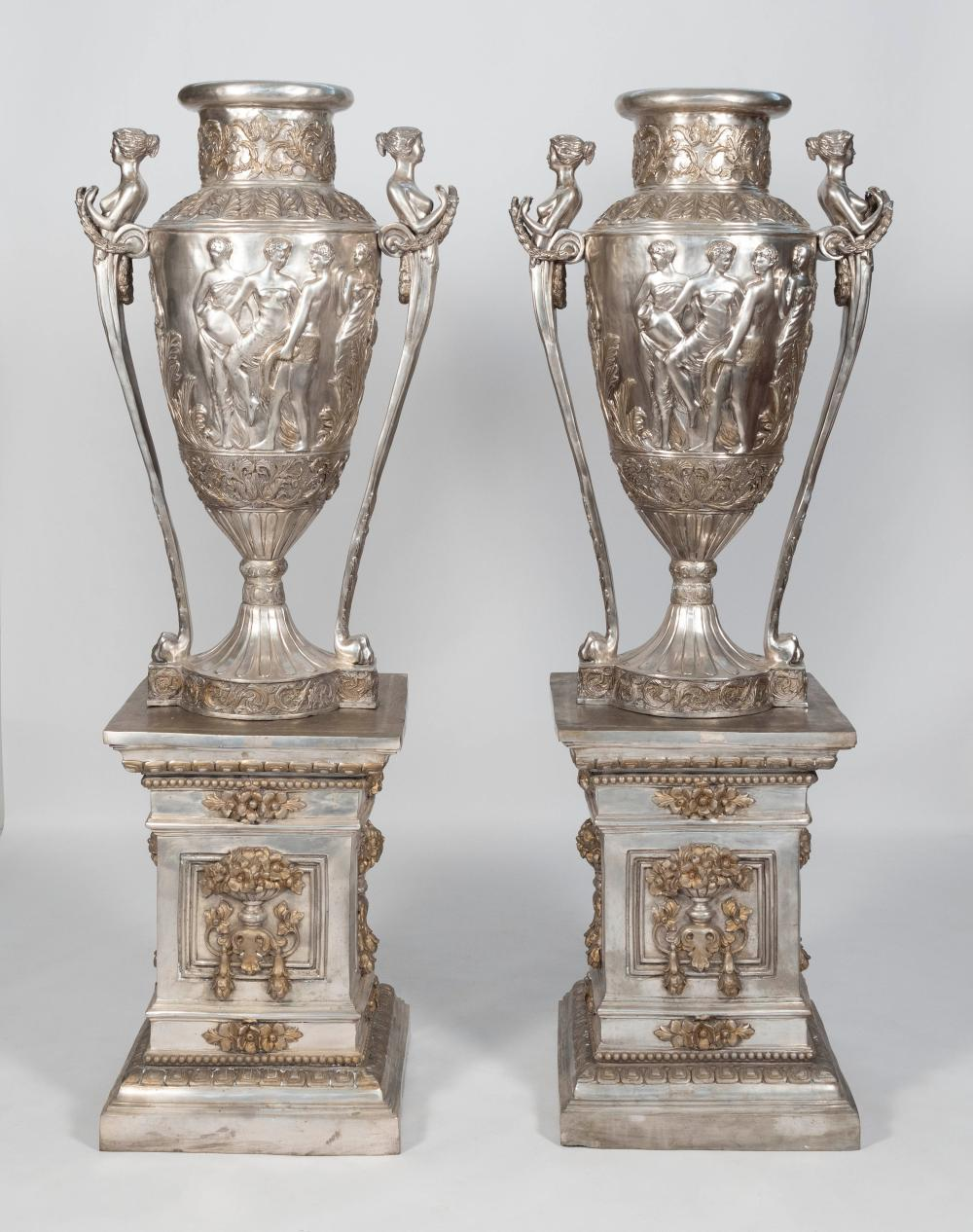 PAIR OF MONUMENTAL NEOCLASSICAL METAL URNS ON PEDESTALS The urns with scantily clad figures in relief and caryatid handles. Pedestal...