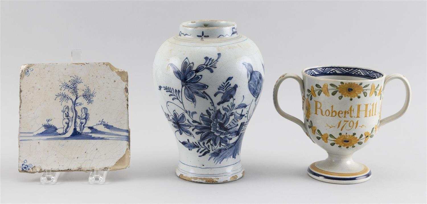 "TWO PIECES OF ANTIQUE DELFT AND A SOFT-PASTE CUP A Delft vase with blue and white floral decoration, height 7.25"", a Delf tile with..."
