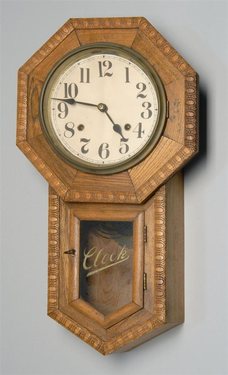 """WALL CLOCK Oak case. Paper dial with Arabic numerals. Lower reverse-painted tablet inscribed """"Clock"""". Height 21.75""""."""