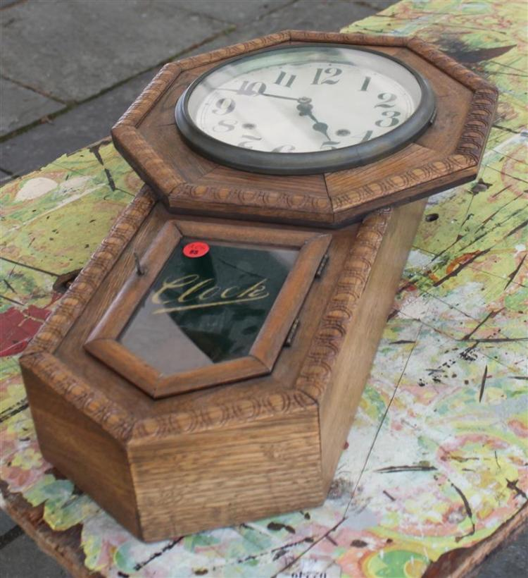 WALL CLOCK Oak case. Paper dial with Arabic numerals. Lower reverse-painted tablet inscribed