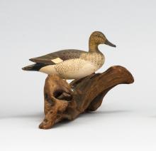 "JAMES LAPHAM MINIATURE GADWALL DRAKE Circa 1955. Raised feather detail. Mounted on a driftwood base. Signed on underside of base ""Ga..."