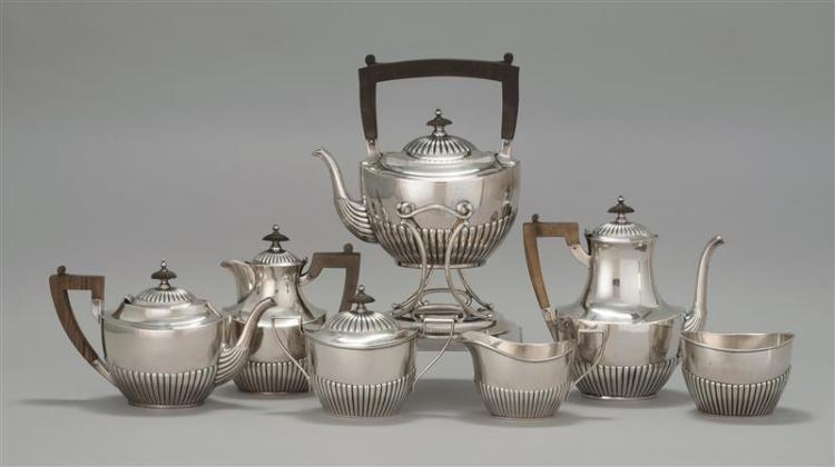 GORHAM SEVEN-PIECE STERLING SILVER TEA SET In half-rib form with ebony handles. Includes a hot water kettle on stand, a coffeepot, h...