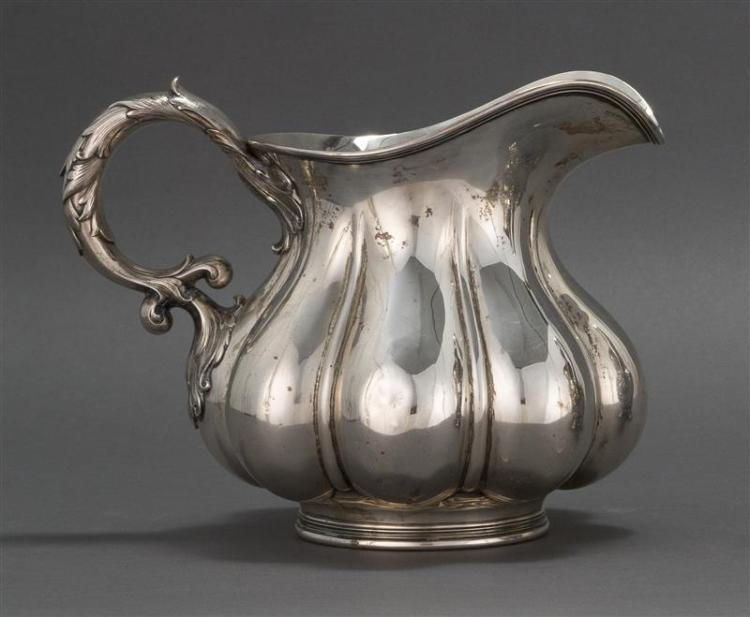 WHITING STERLING SILVER WATER PITCHER Squat lobed body with chased foliate handle. Monogrammed on side and presentation inscription...