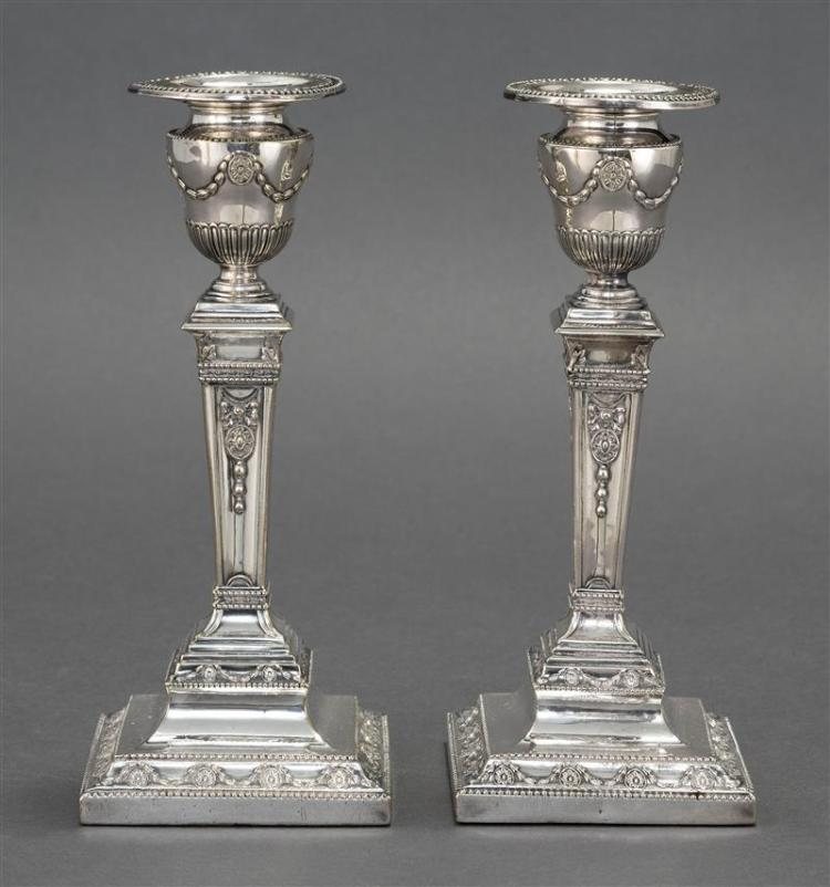 PAIR OF ENGLISH SILVER PLATED CANDLESTICKS Removable bobèches with beaded rims. Urn-form socles atop square ribbed and tapered pedes...