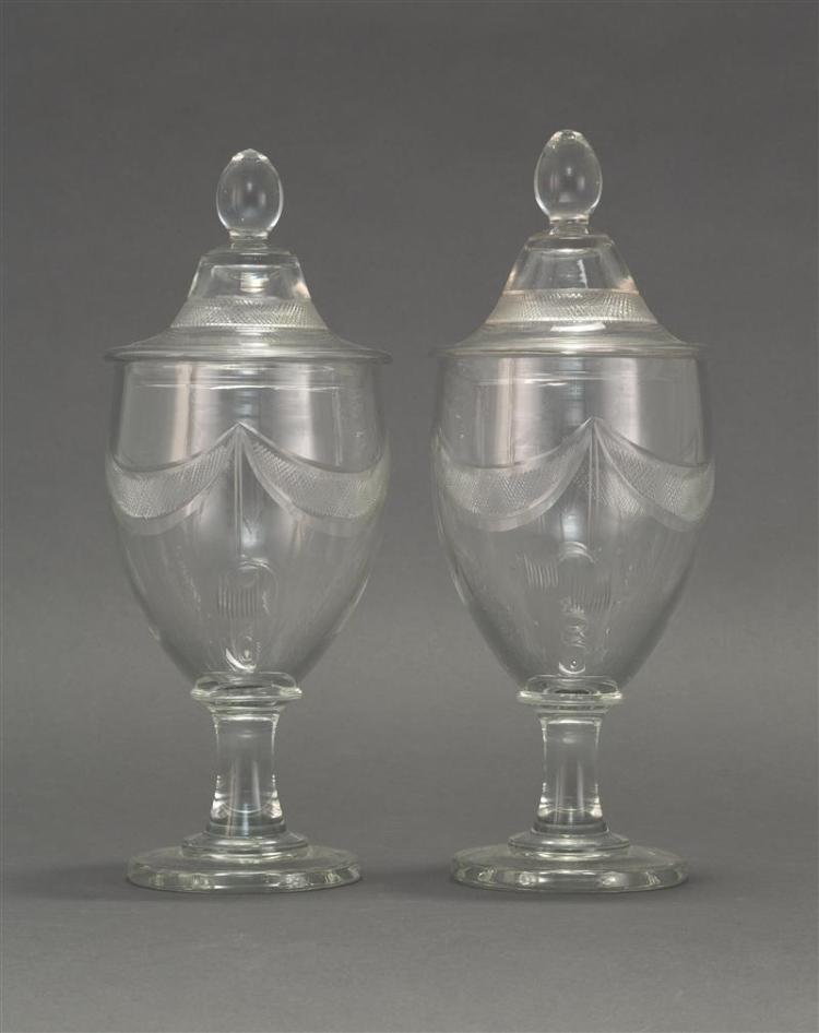 PAIR OF BLOWN GLASS COVERED POKALS Covers with cut faceted finials and crosshatch banding. Urn-form bodies with drape and swag cross...
