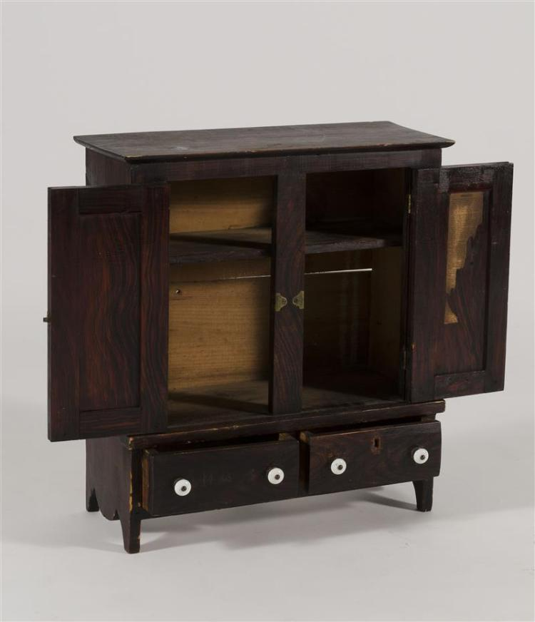 MINIATURE CUPBOARD In pine under a red and black grain-painted finish. Two paneled doors open to reveal a single interior shelf. Two...