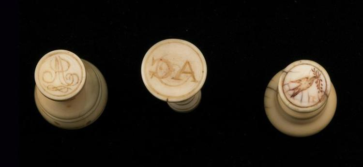 THREE WHALE IVORY SEALING WAX STAMPS One with red incised bands. One stamps an image of a dove and an olive branch. Two stamp initia...
