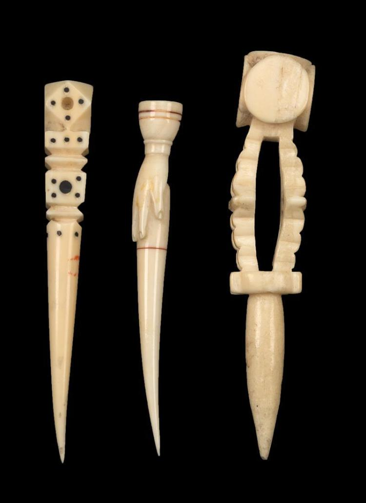 """THREE WHALEBONE AND WHALE IVORY BODKINS One with a hand-form terminal and incised red lines, length 3.5"""". One with geometric carved..."""