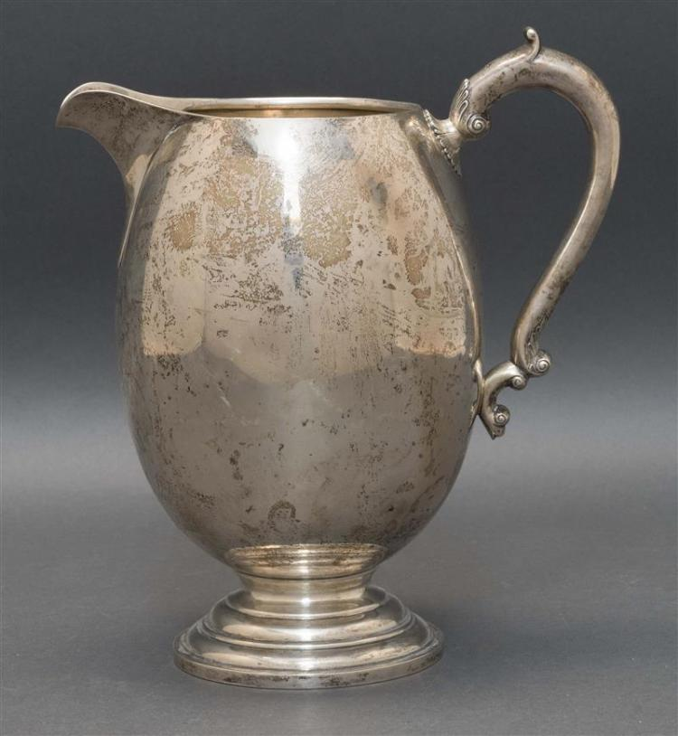 "TUTTLE STERLING SILVER WATER PITCHER In egg form with hollow foliate handle and molded foot. Monogrammed ""LSS"". Height 10"". Approx...."