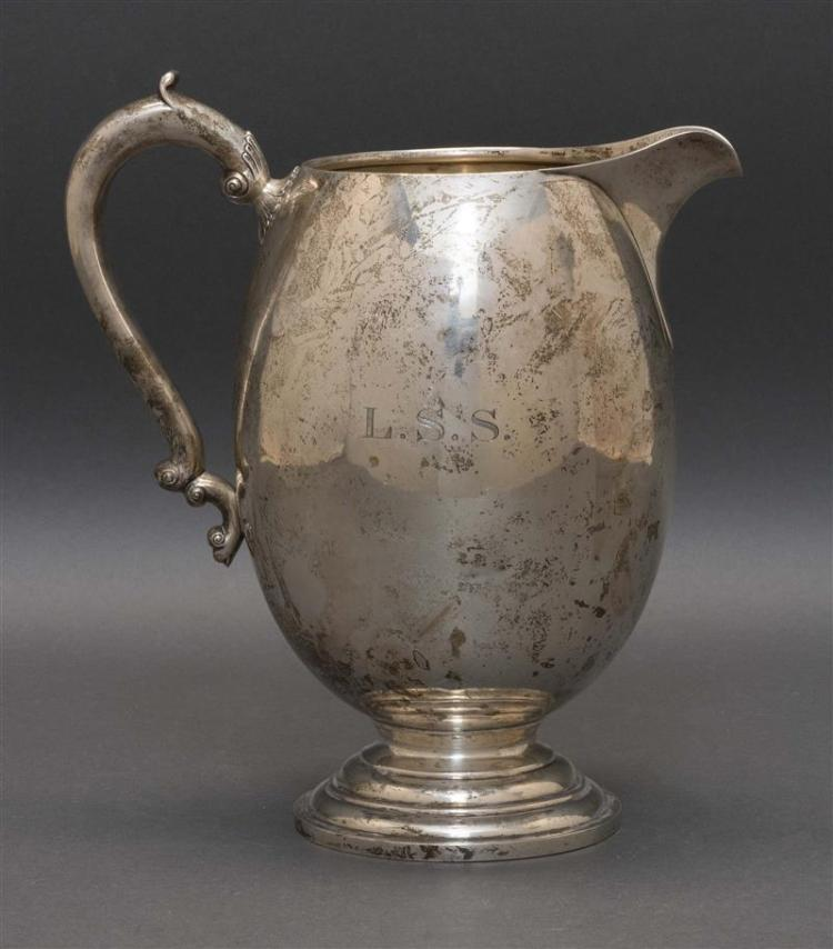 TUTTLE STERLING SILVER WATER PITCHER In egg form with hollow foliate handle and molded foot. Monogrammed