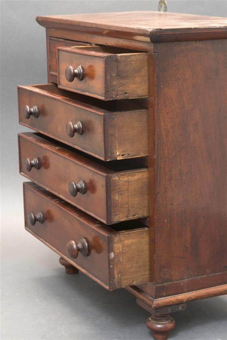 MINIATURE FIVE-DRAWER CHEST In mahogany and mahogany veneer. Pine secondary woods. Two small drawers over three full-width drawers....