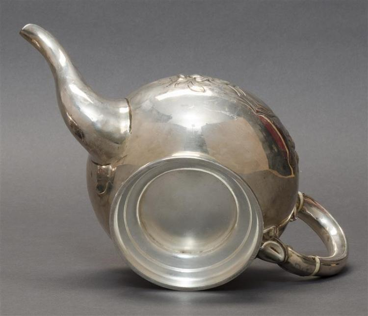 BULLET-FORM SILVER TEAPOT Unmarked. Repoussé decoration and hand-chased with floral bouquets, scrolling foliage and vacant shields....