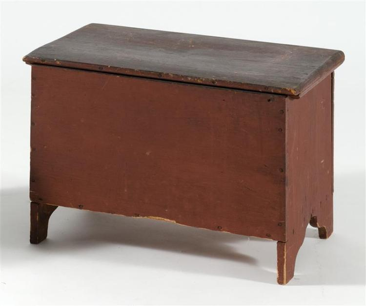 """MINIATURE LIFT-TOP BLANKET CHEST In pine under red paint. Interior ditty box. Bootjack ends. Height 13"""". Width 19.25"""". Depth 12""""."""
