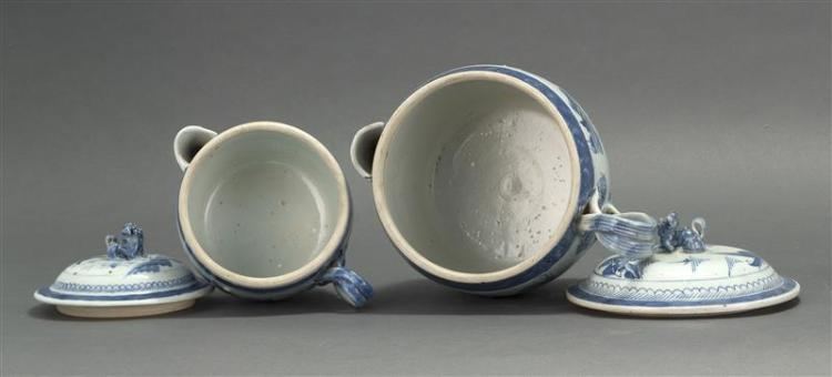 TWO CANTON PORCELAIN COVERED CIDER PITCHERS Both with strap handles and foo dog finials. Blue and white decoration. Heights 7