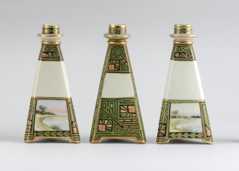 THREE NIPPON PORCELAIN CANDLESTICKS Triangular, with a green geometric pattern and landscape decoration. Van Patten #47 mark on base...