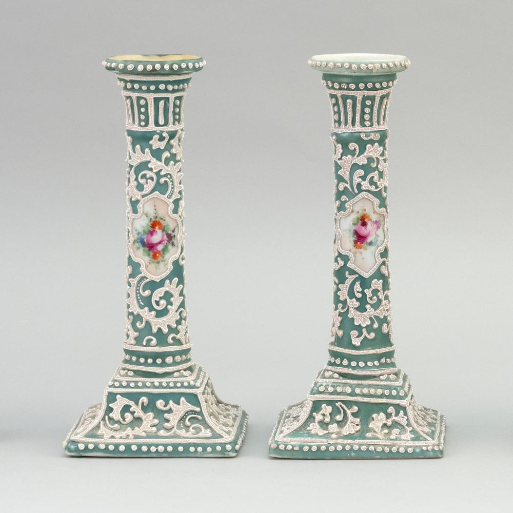 """PAIR OF MORIAGE NIPPON PORCELAIN CANDLESTICKS With floral cartouches on a green and white floral ground. Heights 9.4""""."""