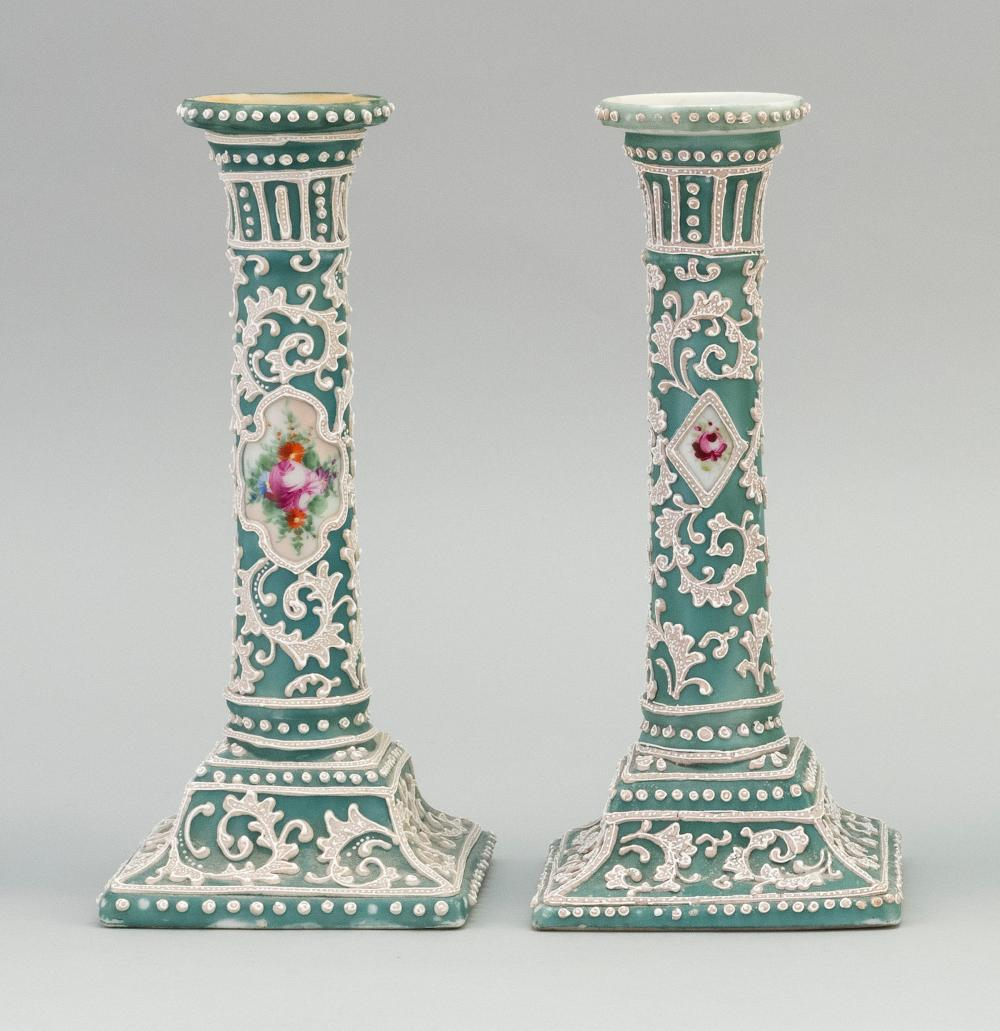 PAIR OF MORIAGE NIPPON PORCELAIN CANDLESTICKS With floral cartouches on a green and white floral ground. Heights 9.4