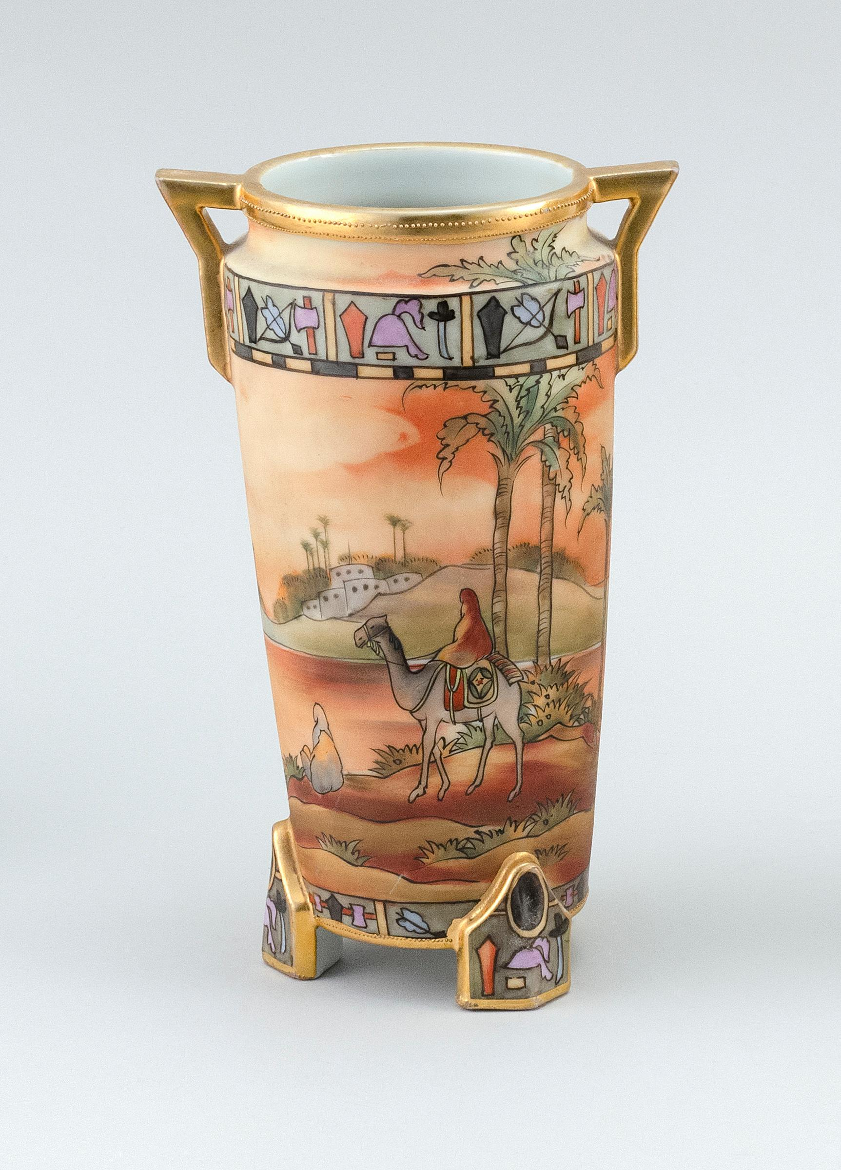 NIPPON PORCELAIN VASE Cylindrical, with openwork handles, tripod base and decoration of an Egyptian landscape with camel rider. Van...