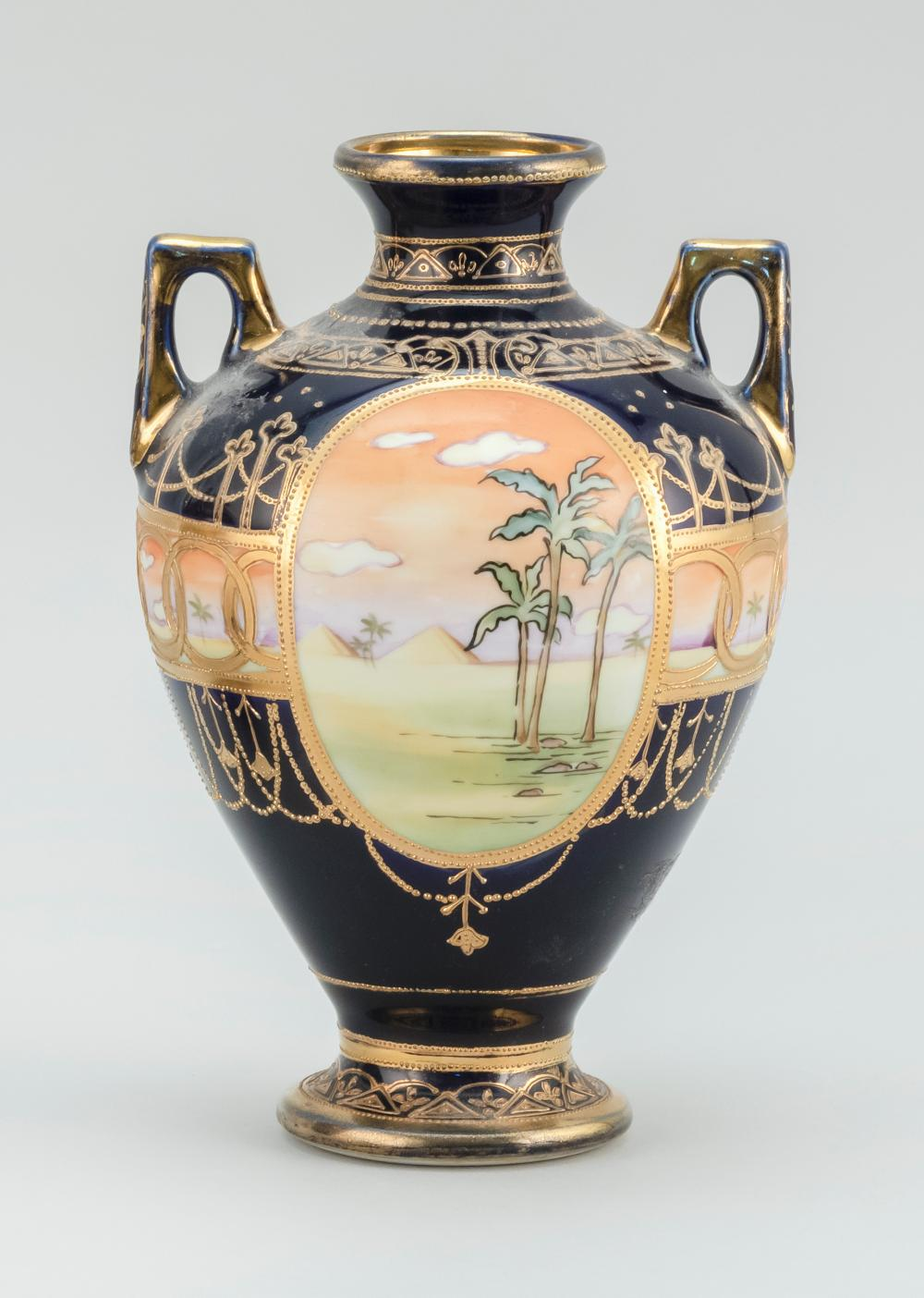 NIPPON PORCELAIN VASE In urn form, with cartouches of ostriches in an Egyptian landscape on a cobalt blue and gilt ground. Van Patte...