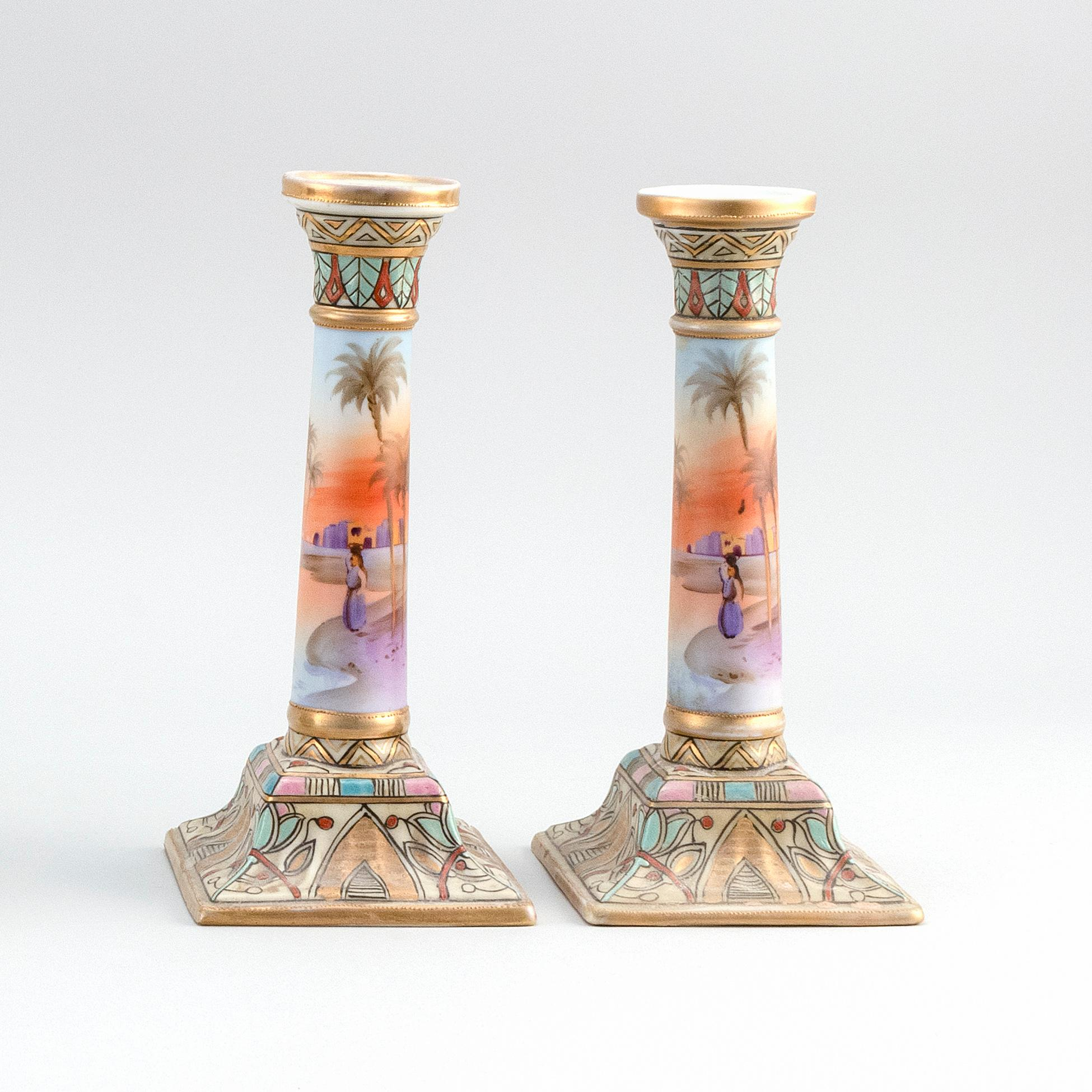 """PAIR OF NIPPON PORCELAIN CANDLESTICKS With Egyptian landscape decoration. Van Patten #47 mark on bases. Heights 9.2""""."""