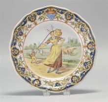 FRENCH FAÏENCE CERAMIC PLATE With polychrome decoration of a woman carrying a jug of milk with a gentleman and cows in the distance....