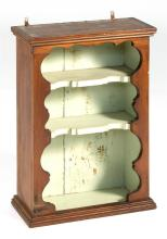 ANTIQUE HANGING SHELF Under brown paint with shaped border. Three-shelved interior painted mint green. Height 25.75