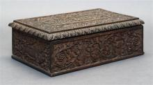 CARVED HARDWOOD LIFT-TOP BOX Intricately detailed floral and foliate decoration surrounding figural and animal depictions on each fa...