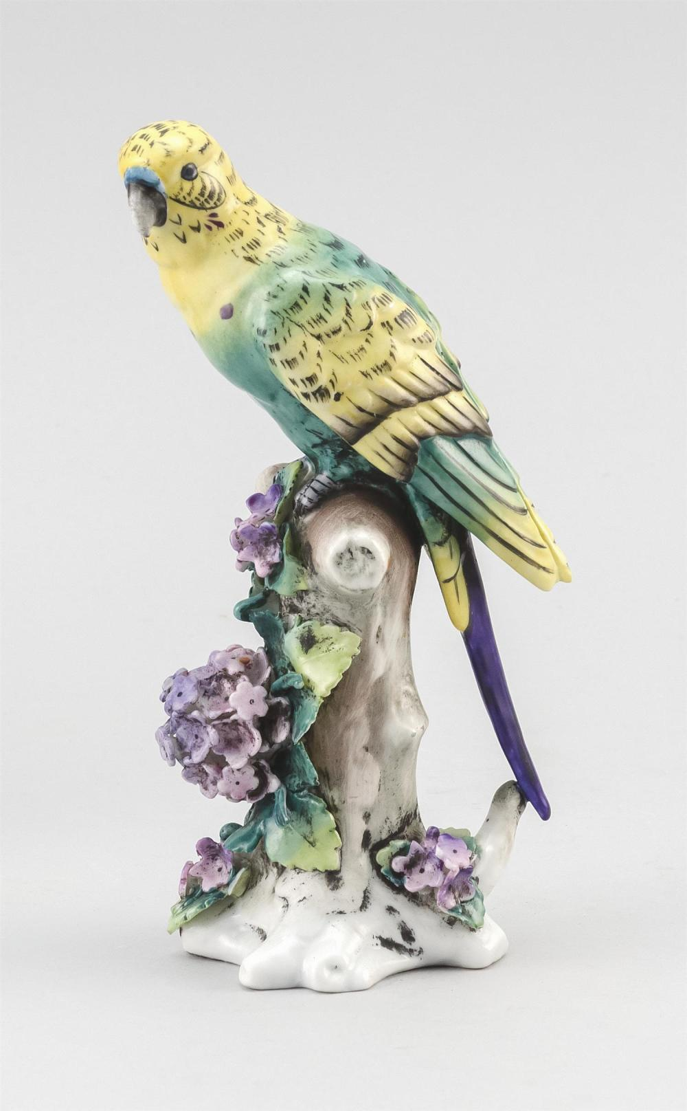 """CAPODIMONTE-STYLE PORCELAIN PARAKEET FIGURE Perched on a flowering branch. Over-glaze blue crowned N mark. Paper label. Height 6.5""""."""