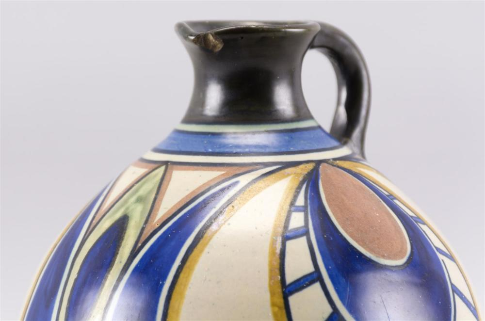 GOUDA POTTERY JUG With stylized foliate ornament in shades of matte blue, yellow, green and pink. Signed on bottom