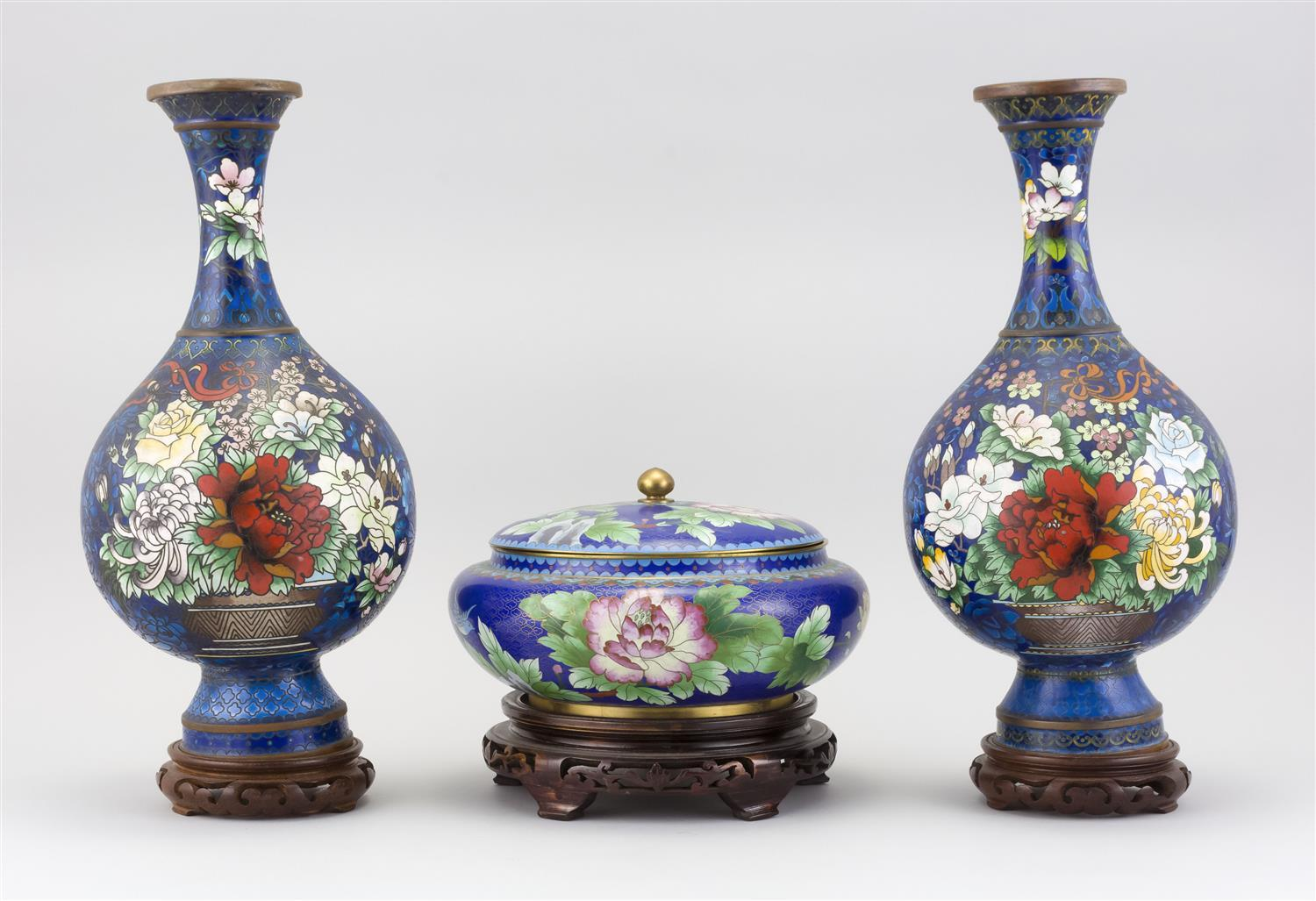THREE PIECES OF CHINESE CLOISONNÉ ENAMEL A pair of vases with polychrome floral decoration on a blue ground, and a lidded bowl with...