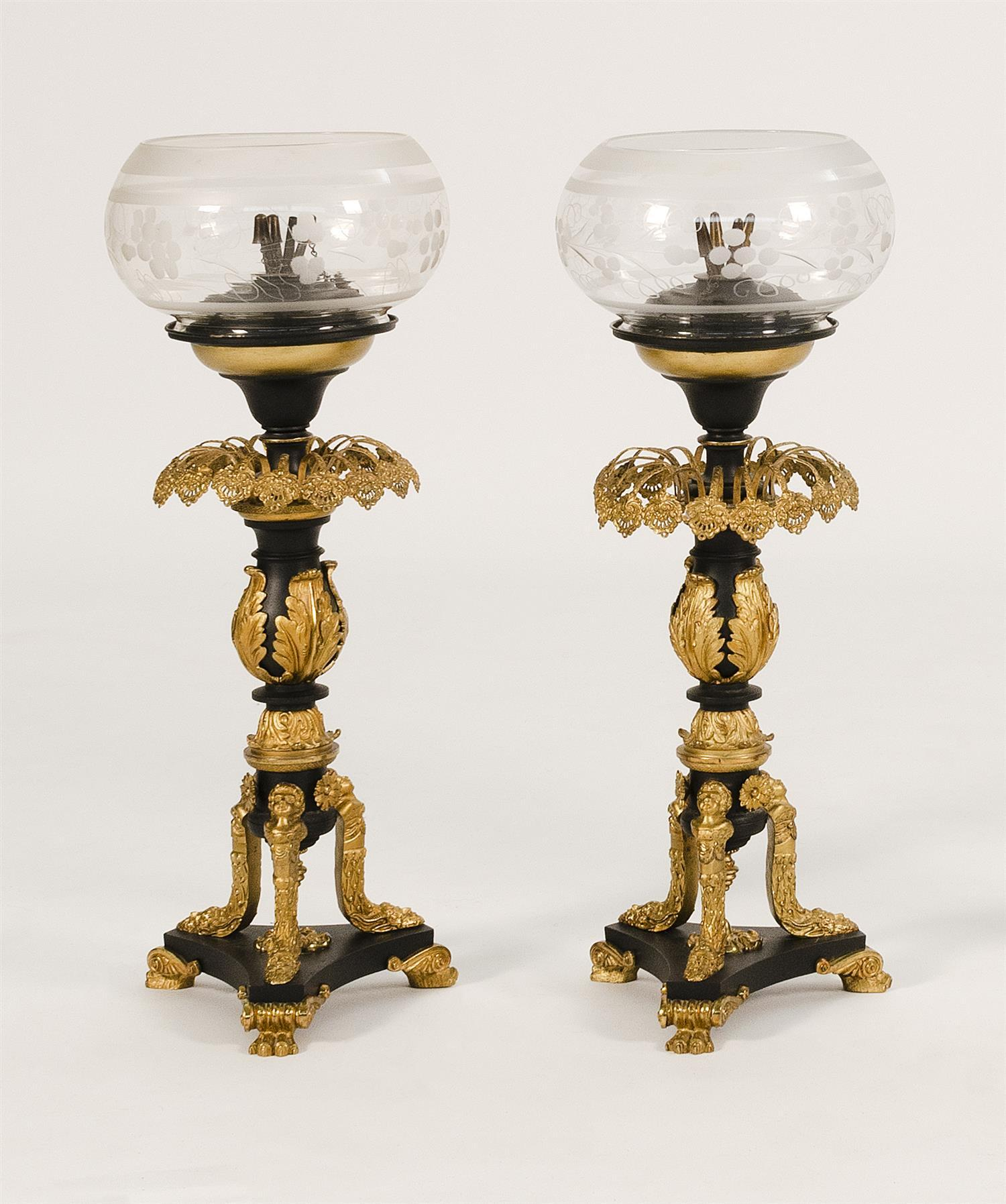 PAIR OF PARCEL-GILDED CAST METAL SINUMBRA LAMPS Shades with floral design. Neoclassical bases adorned with foliage and masks. Height...