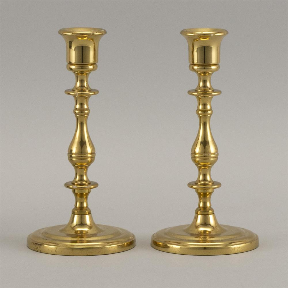 """PAIR OF BRASS CANDLESTICKS With balustroid stems and circular molded feet. Heights 6.75""""."""
