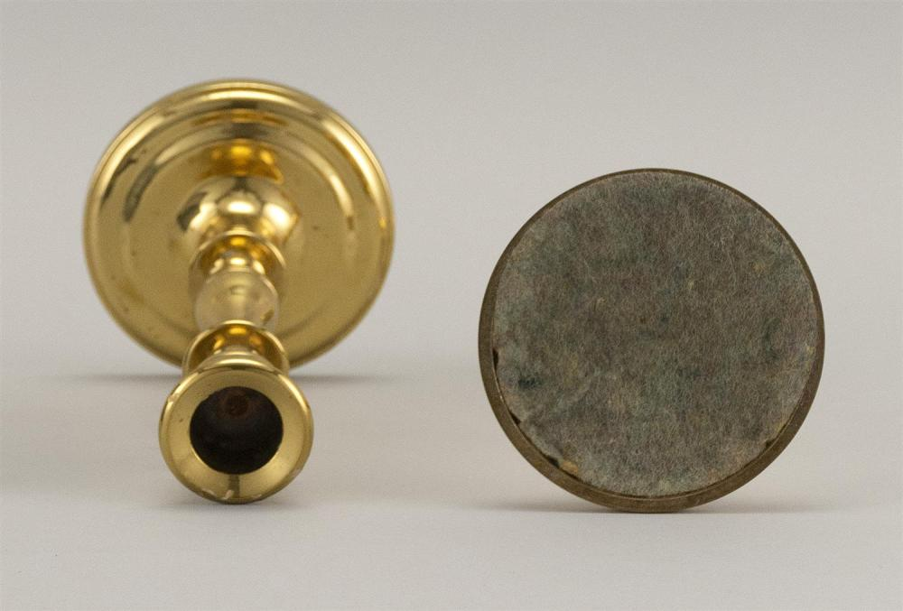 PAIR OF BRASS CANDLESTICKS With balustroid stems and circular molded feet. Heights 6.75