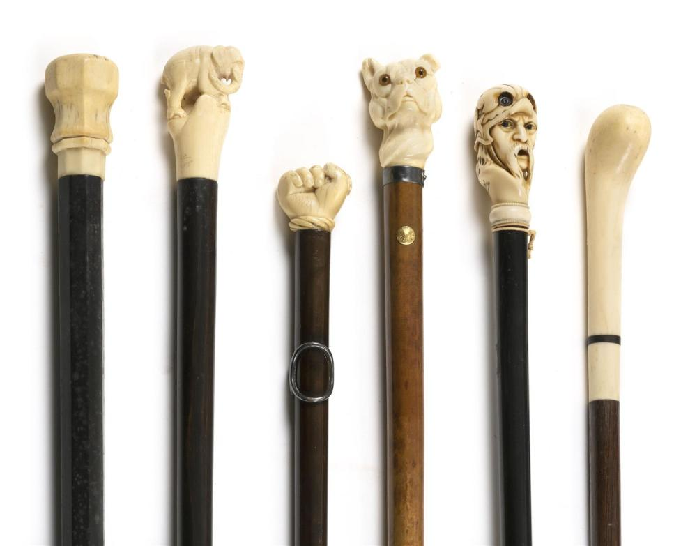SIX CANES WITH CARVED IVORY HANDLES Two knob handles. Others carved in the form an elephant, a bulldog, a fist and a man's face. All..