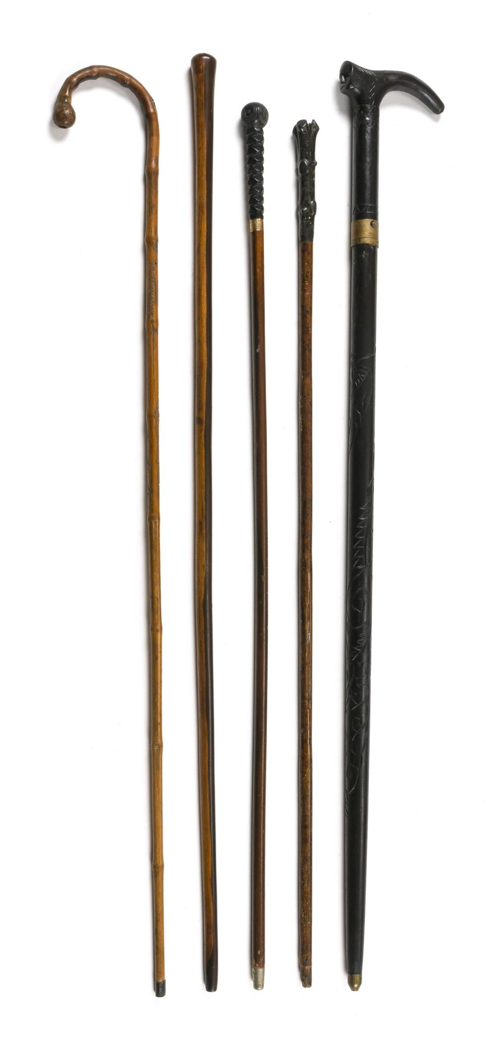 "FIVE CARVED WOODEN CANES Two with metal collars. Lengths from 34"" to 36""."