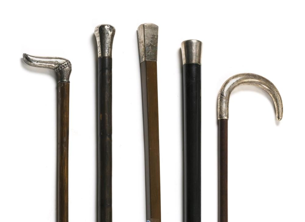 FIVE CANES WITH STERLING SILVER HANDLES Handles in assorted shapes and designs. All with wooden shafts. Four with silvered metal fer...