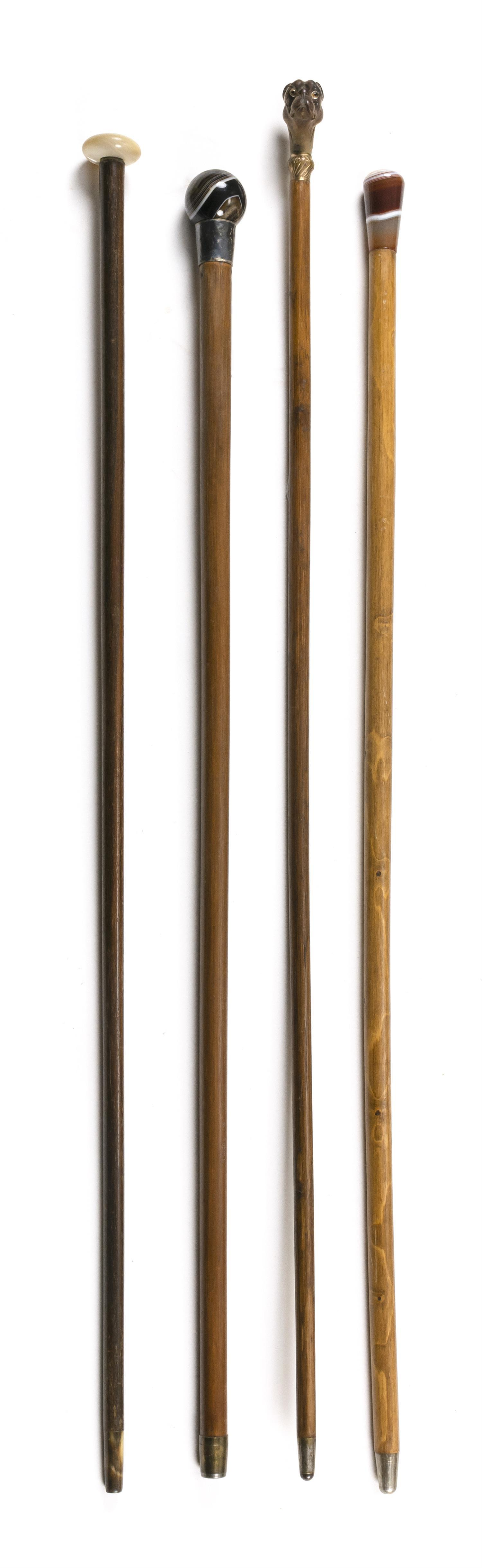 FOUR CANES Two with swirled glass handles, one with a mother-of-pearl flattened ball handle, and one with wooden handle carved in th...
