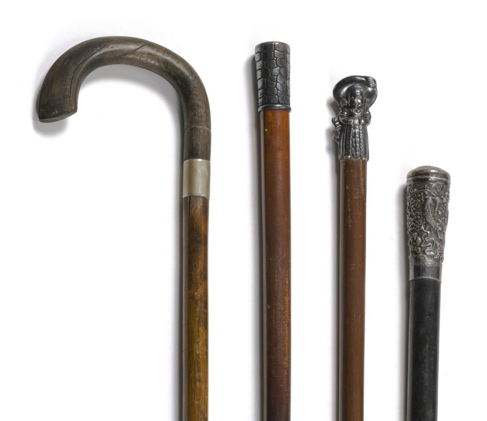 FOUR CANES One with a wooden crook handle and three with metal handles, one with a Chinese dragon design and one in the form of a ch...