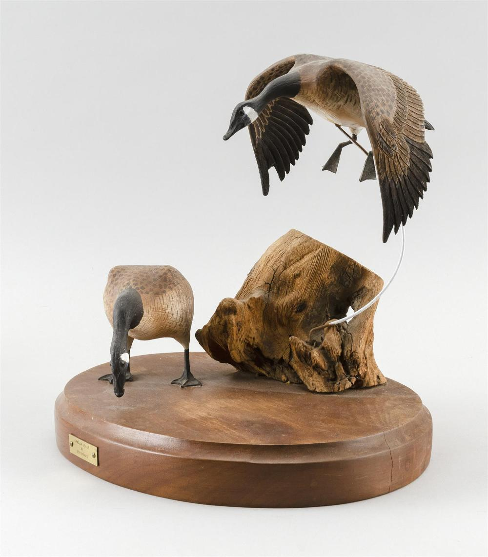 PAIR OF BOB MIMMS MINIATURE GEESE One in flying position and one in feeding position. Mounted together on an oval wooden base. Heigh...