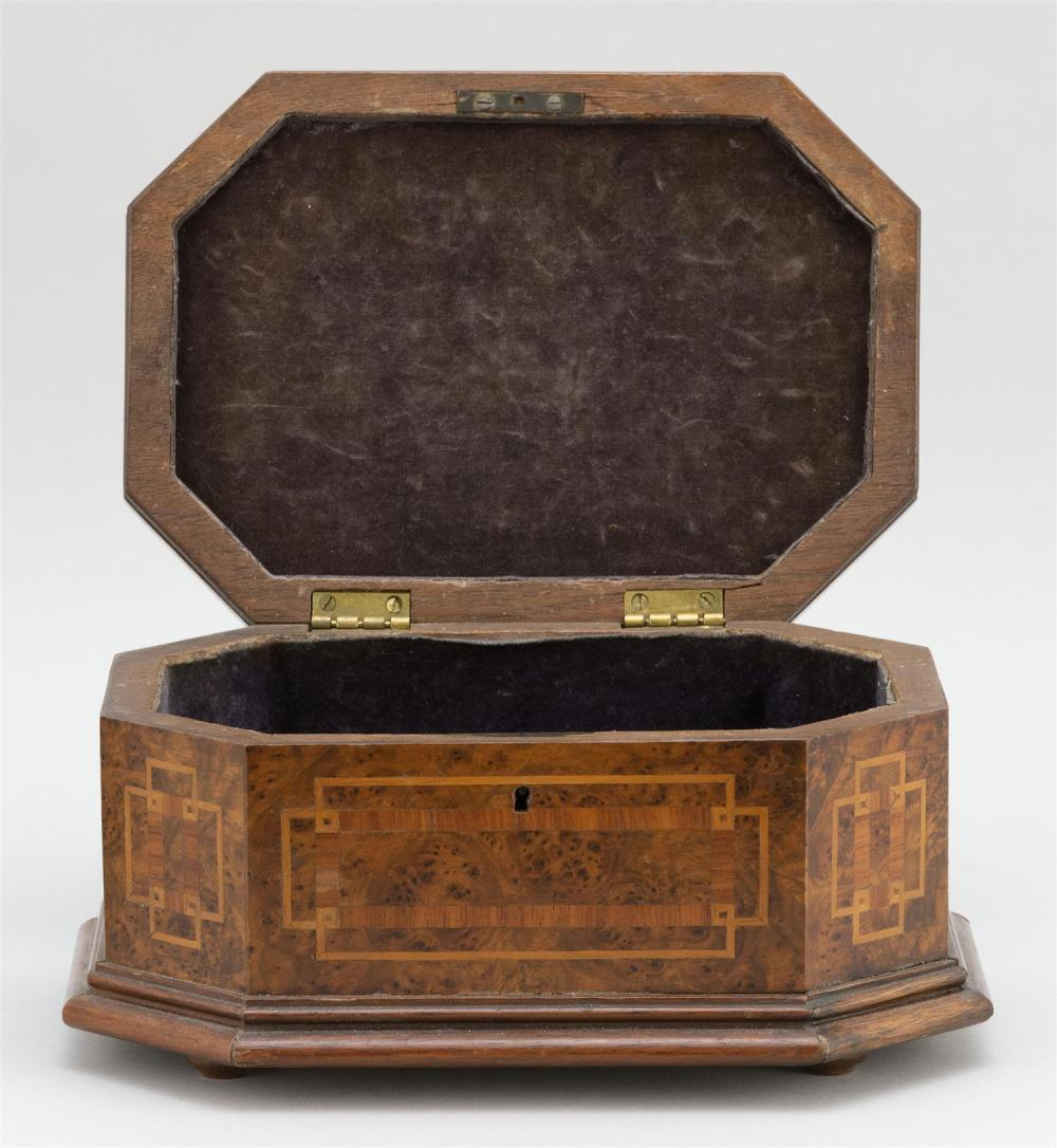 OCTAGONAL BURLED WALNUT AND FRUITWOOD VENEER BOX Lift top with floral urn inlay. Interior lined with black velvet. Bun feet. Width 8...
