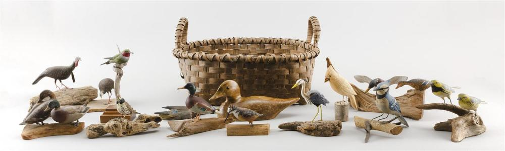 THIRTEEN MINIATURE AND LIFE-SIZE BIRD CARVINGS IN A SPLINTWORK HANDLED BASKET Birds by assorted makers. Includes a hummingbird by Gr...