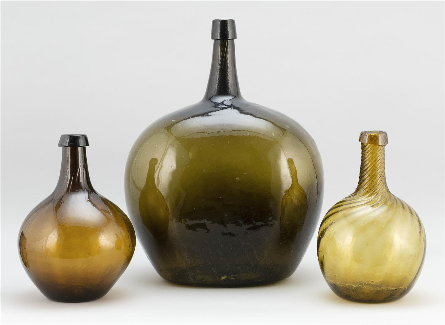 "THREE GLASS DEMIJOHNS One olive green, height 17"", and two amber with swirled necks, heights 11""."