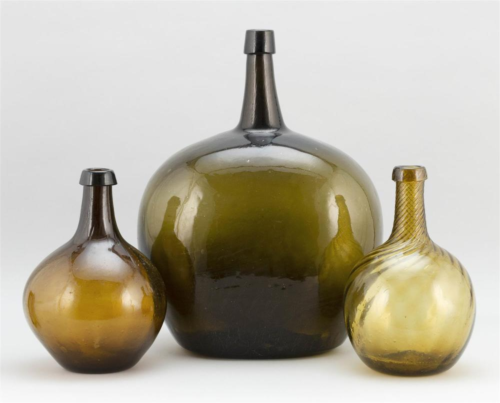 THREE GLASS DEMIJOHNS One olive green, height 17