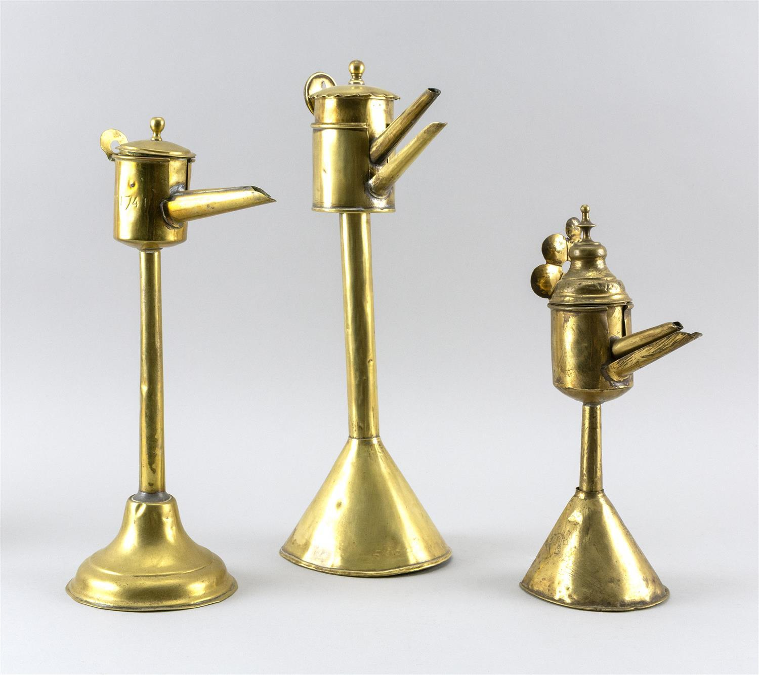 """THREE FLEMISH BRASS SPOUT LAMPS Heights from 11"""" to 14""""."""